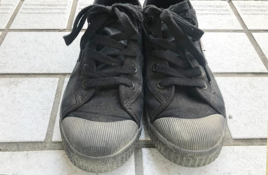 砂埃で白くなった黒い靴